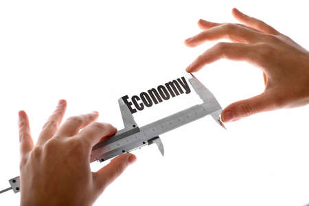 Close up shot of two hands holding a caliper and measuring the word Economy