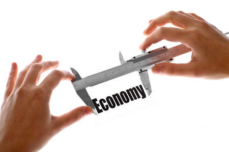 exact: Close up shot of two hands holding a caliper and measuring the word  Economy