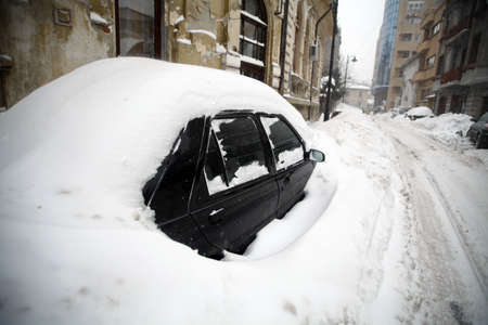 A car is covered with snow on a street Stock Photo