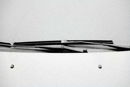 Close-up shot of a cars windscreen wiper covered in snow photo