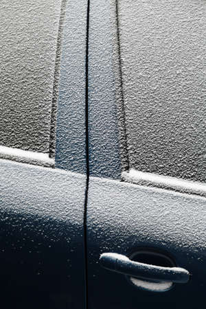 Close-up shot of a cars door covered in snow photo