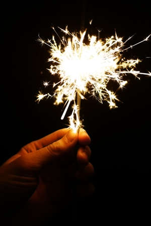 Color shot of a hand holding a sparkler photo