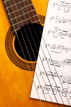 A classical guitar and a music sheet. photo