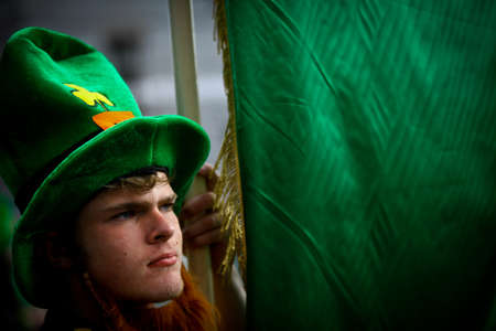 Bucharest, Romania - March 16, 2014: A man holds a green flag during a parade celebrating Saint Patricks day in Bucharest, Romania.  Saint Patrick is the patron saint of Ireland and credited with bringing Christianity to Ireland.