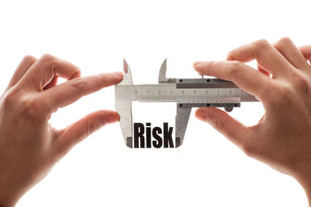 reduce risk: Close up shot of a caliper measuring the word Risk