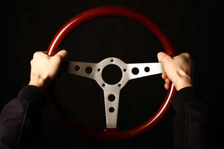Detail of two hands holding a wooden vintage steering wheel on black. photo