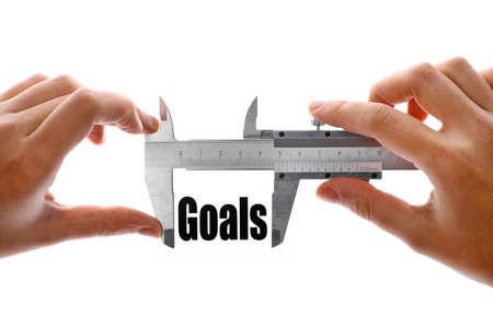 Close up shot of a caliper measuring the word Goals photo