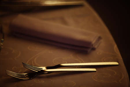 dinner party: Two forks on a dinner table in a restaurant.