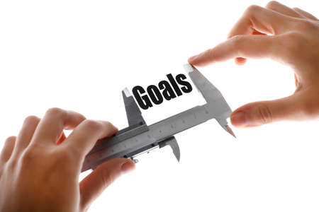 Close up shot of a caliper measuring the word Goals. photo