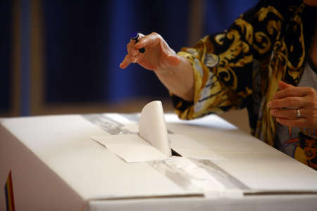 encuestando: La mano de una persona emita su voto en un colegio electoral durante la votaci�n.