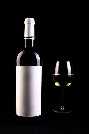 alcohol bottles: Wine bottle with a white blank label and a glass.