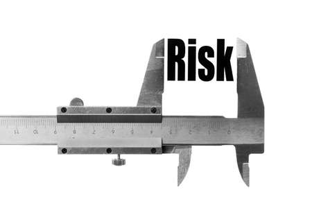 measurements: Close up shot of a caliper measuring the word Risk. Stock Photo