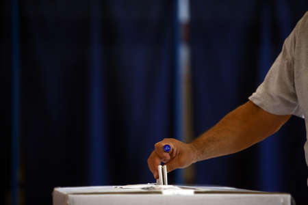 polling station: Hand of a person casting a ballot at a polling station during voting. Stock Photo