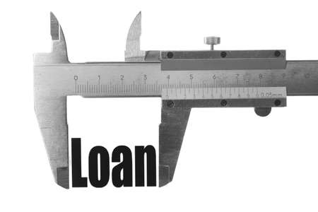 Close up shot of a caliper, measuring the word Loan. photo