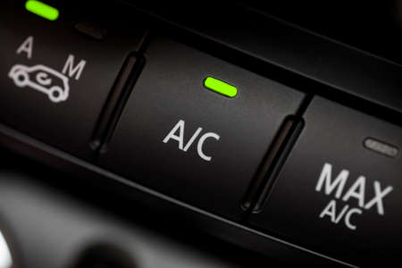 Color detail with the air conditioning button inside a car.