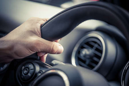 Detail of a hand holding a steering wheel.