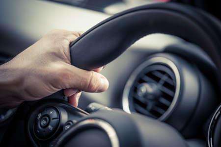 Detail einer Hand, die ein Lenkrad.