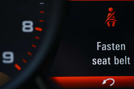 car dashboard: Color detail of the seat belt icon on the dashboard of a car.