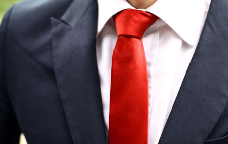 red tie: Business man wearing a suit with a red tie. Detail on the tie. Stock Photo