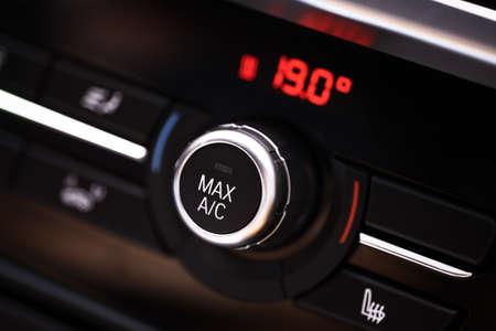 aire acondicionado: Detalle de color con el botón del aire acondicionado en el interior de un coche.