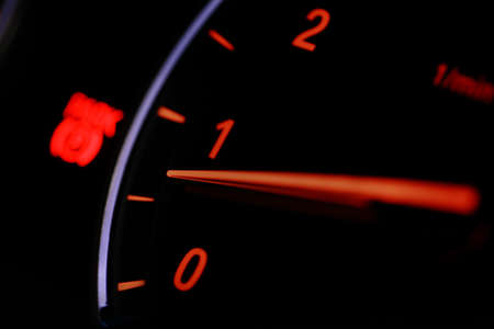 Close up shot of a tachometer in a car, at night. photo