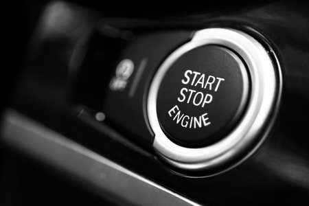 stop: Detail on a black start button in a car.