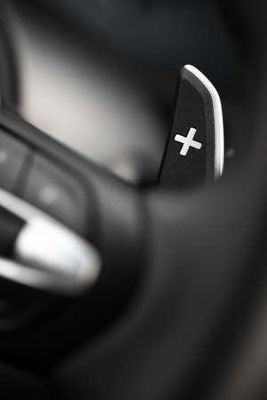 Close up shot of a manual gear changing paddle on a cars steering wheel. photo