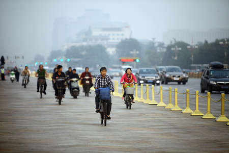 smog: Beijing, China - September 25, 2014: People ride their bicycles on the streets of Beijing, China.