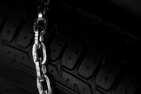 compulsory: Horizontal detail shot of some new snow chains on a cars tire.