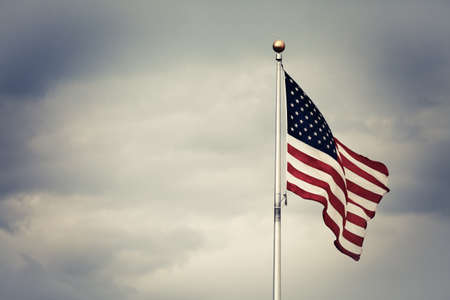 flag pole: Color picture of the U.S. flag against a cloudy sky. Stock Photo