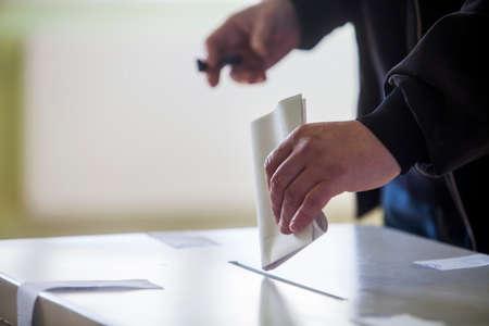 Hand einer Person wirft einen Stimmzettel in einem Wahllokal in Abstimmung. Standard-Bild
