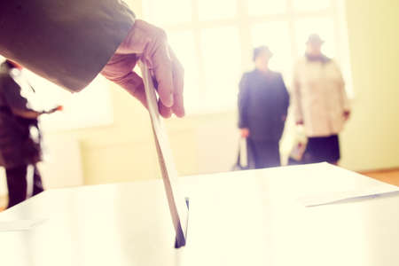 Hand of a person casting a ballot at a polling station during voting. Imagens