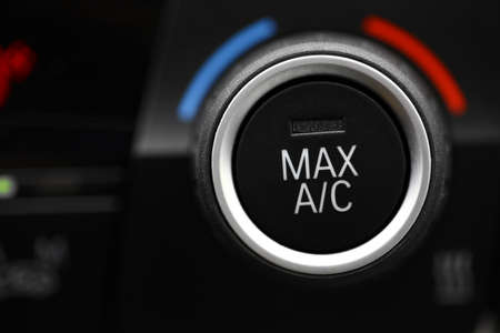 cold air: Color detail with the air conditioning button inside a car.