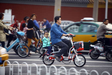 Beijing, China - September 25, 2014: People ride their bicycles and motorcycles on the streets of Beijing, China.