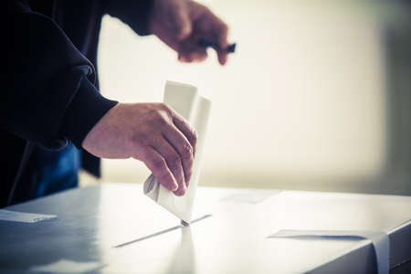 voting: Hand of a person casting a ballot at a polling station during voting. Stock Photo