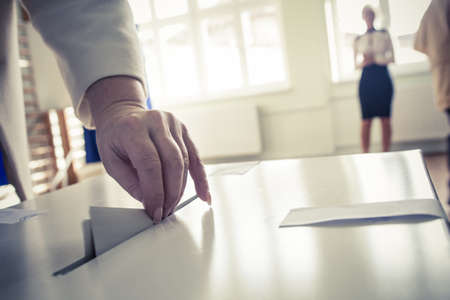 polling: Hand of a person casting a ballot at a polling station during voting. Stock Photo