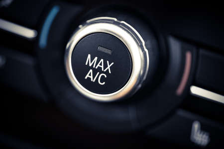 air transport: Color detail with the air conditioning button inside a car.