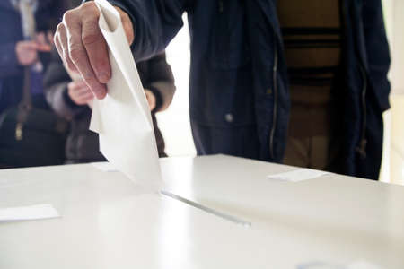 Hand of a person casting a ballot at a polling station during voting. Stockfoto