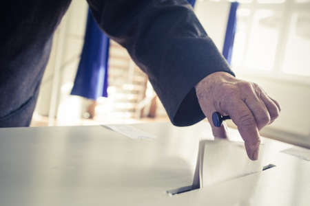 politics: Hand of a person casting a ballot at a polling station during voting. Stock Photo