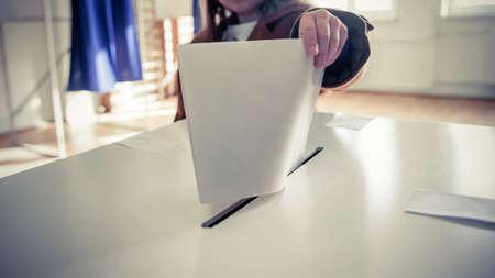 투표시에 투표소에서 투표 용지를 캐스팅하는 사람의 손입니다. 스톡 콘텐츠