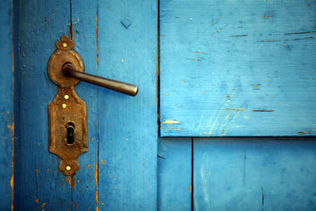 closed: Color shot of a vintage door handle on a wooden blue door.