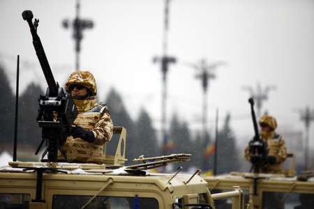 ceremonial clothing: Bucharest, Romania - December 1, 2014: Soldiers ride in Humvees during celebrations for Romanias National Day in Bucharest.