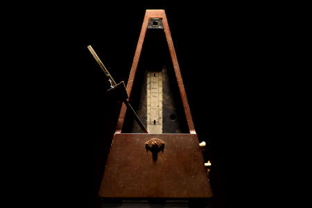 Vertical shot of a vintage metronome, on a black background. photo