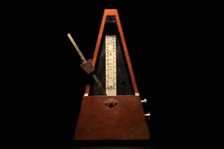 metronome: Horizontal shot of a vintage metronome, on a black .