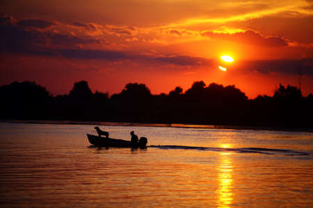 A man rides with his dog in a motorboat, at sunset. photo