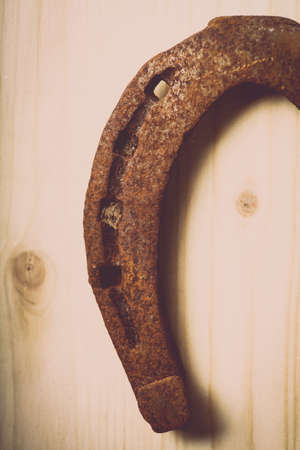 horse shoe: Color shot of a rusty horse shoe on a wooden .