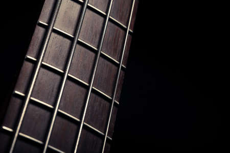 fret: Detail of the fret board of a bass guitar, on a dark . Stock Photo