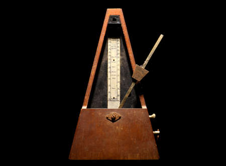 allegro: Horizontal shot of a vintage metronome, on a black background.