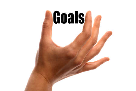 exact: Horizontal shot of a hand squeezing the word Goals between two fingers, isolated on white.