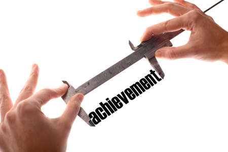 exact: Color horizontal shot of two hands holding a caliper and measuring the word achievement.